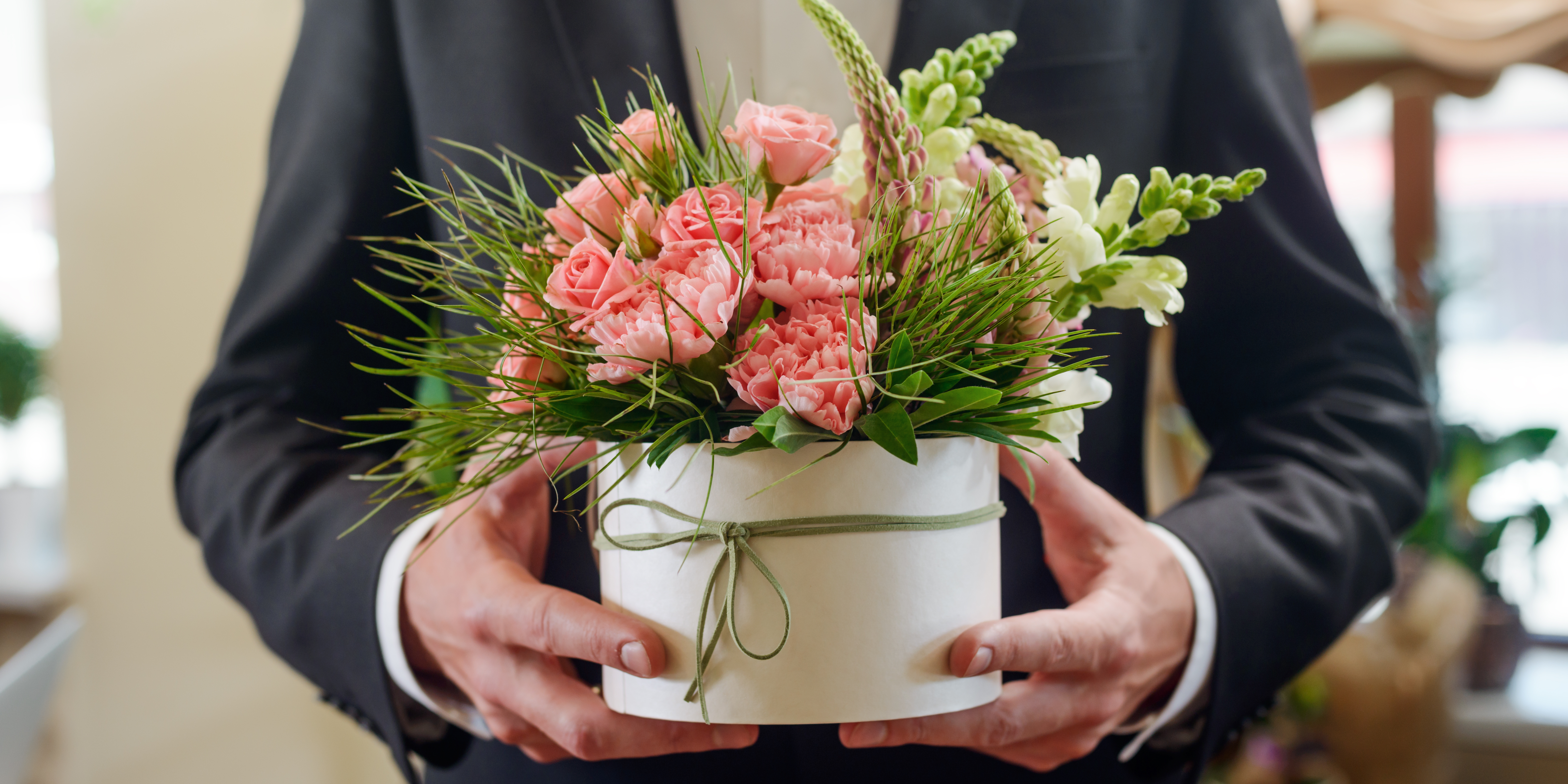 A man in suit carrying a pot of pink flowers